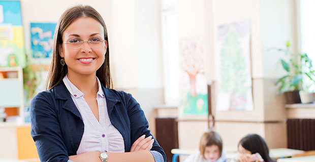 Smiling teacher stands with arms confidently crossed in front of rows of working students