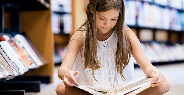 Elementary school girl sitting cross-legged on the floor in the library happily paging through a book perched on her knees