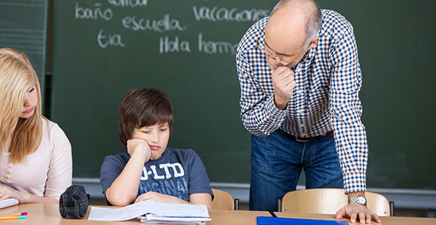 Teacher leaning over student who seems to be frustrated