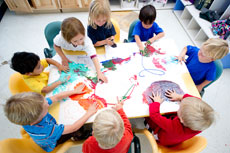 overhead shot of a group of children sitting around a preschool table doing colorful finger-painting