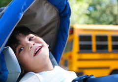 Smiling young boy in adaptive chair with school bus in the background