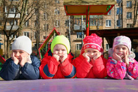 4 kids bundled in winter coats on the playground lean on their hands, listening thoughtfully