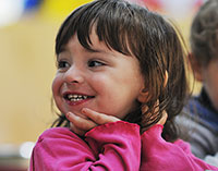 Young smiling girl with chin on hands